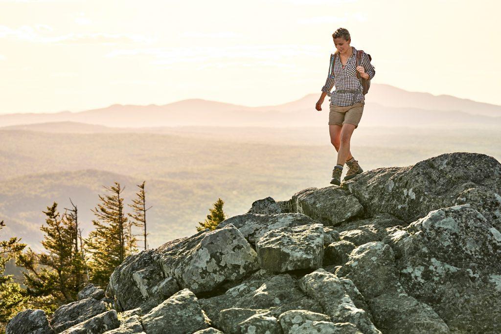 photo of woman hiking across a rocky ridge