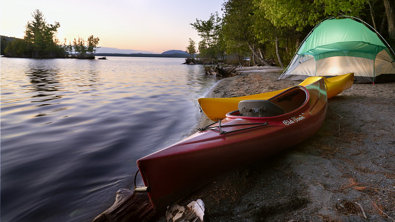 photo of old town kayaks and tent on maine lake
