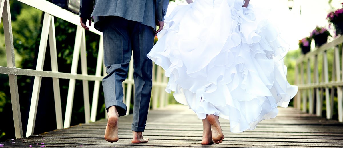 photo of bride and groom walking barefoot across wooden bridge