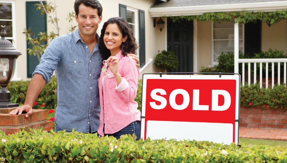 photo of man and woman holding keys in front of house with sold sign