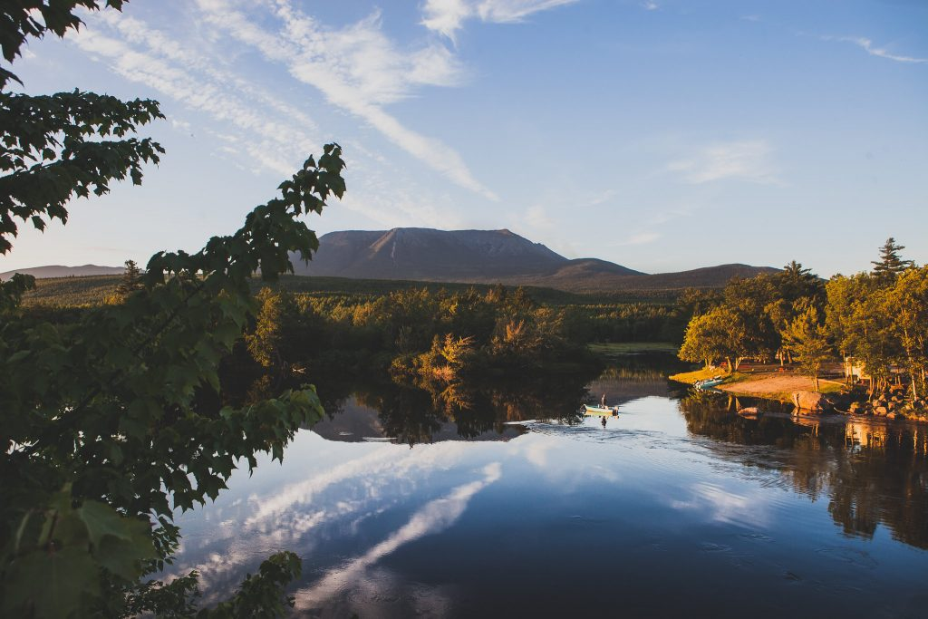 photo of person on boat on lake in baxter state park in front of maine mountain