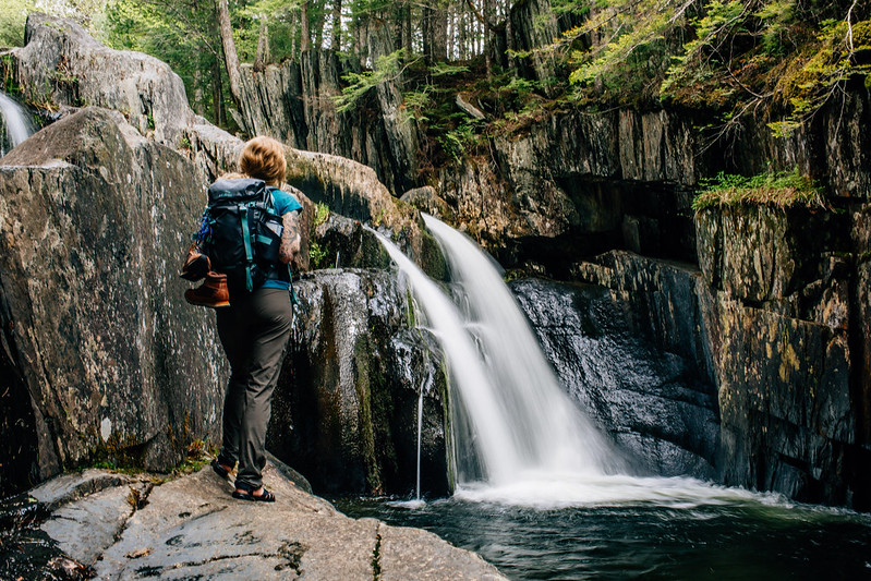 photo of hiker woman standing in front of waterfall