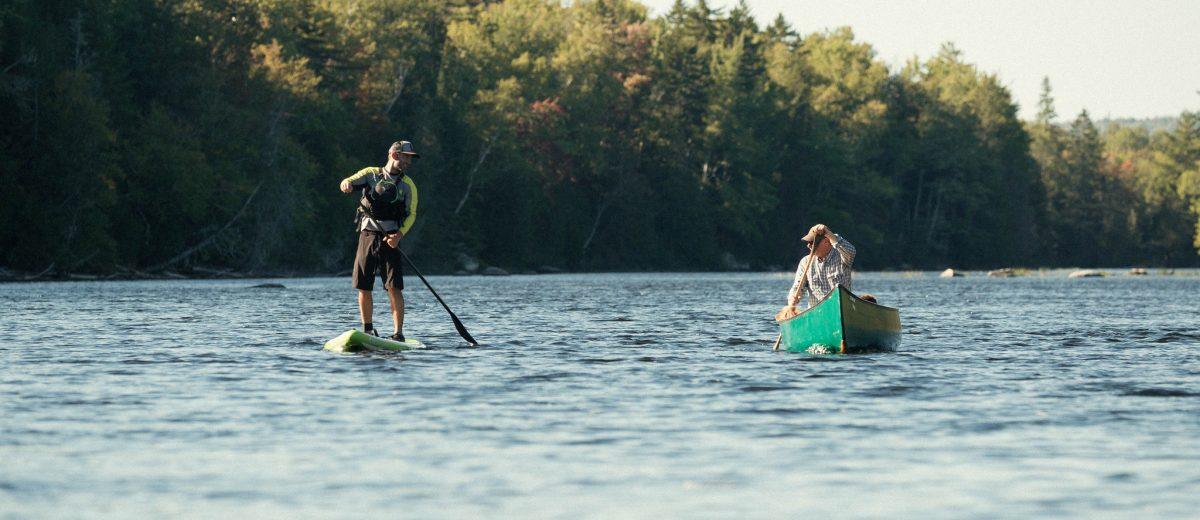 photo of two people in canoe and wake board on maine lake