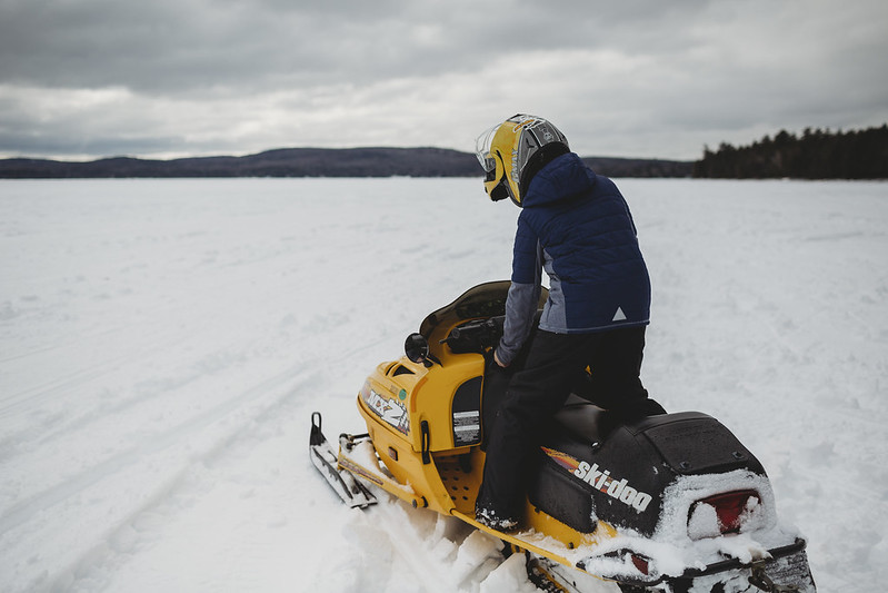 photo of person on snowmobile on maine lake in winter