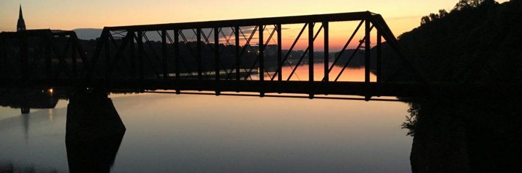 sunset photo of railroad bridge between brewer and bangor maine