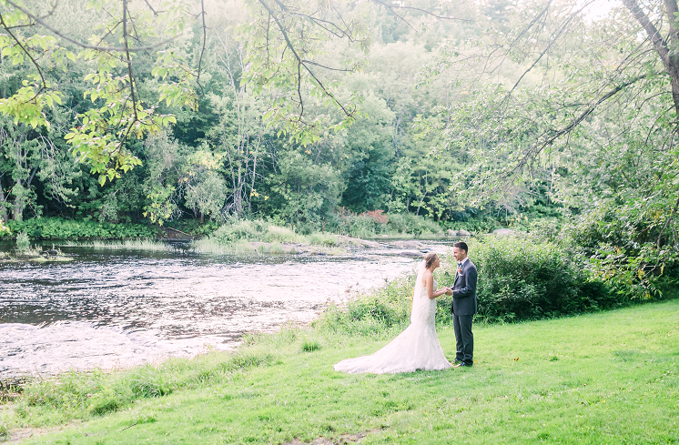 photo of bride and groom standing on hill next to river in the forest