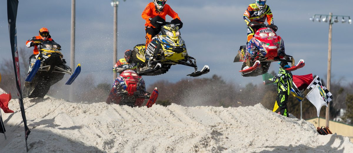 photo of snowmobilers making a jump during a race
