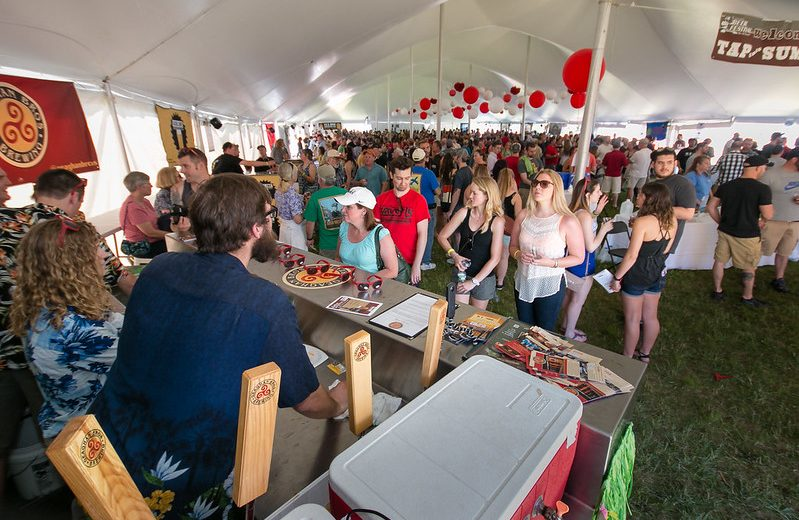 photo of a crowd of people at the geaghan's beer table at the tap into summer beer festival