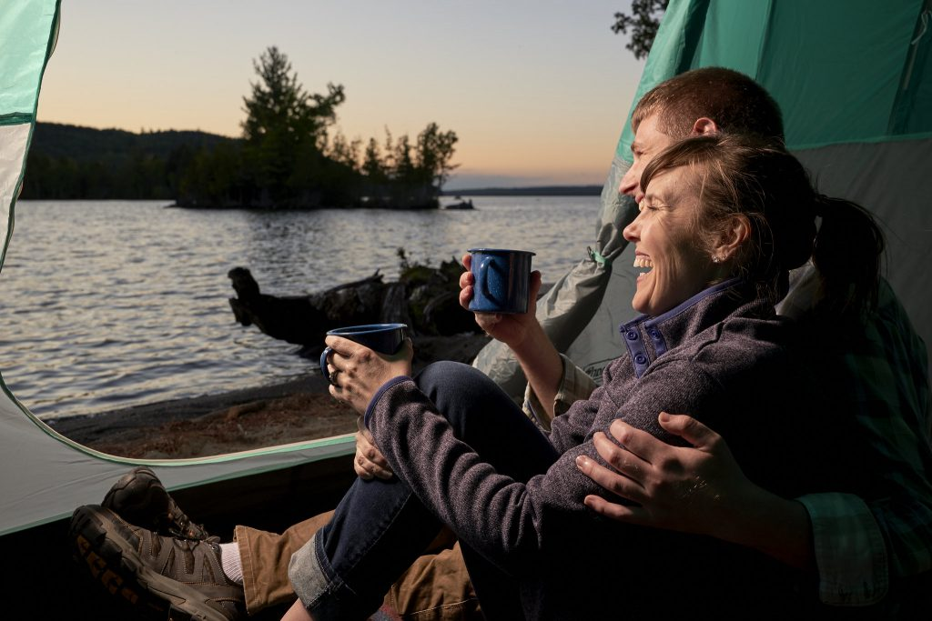 photo of man and woman sitting in tent drinking coffee and enjoying lake sunset