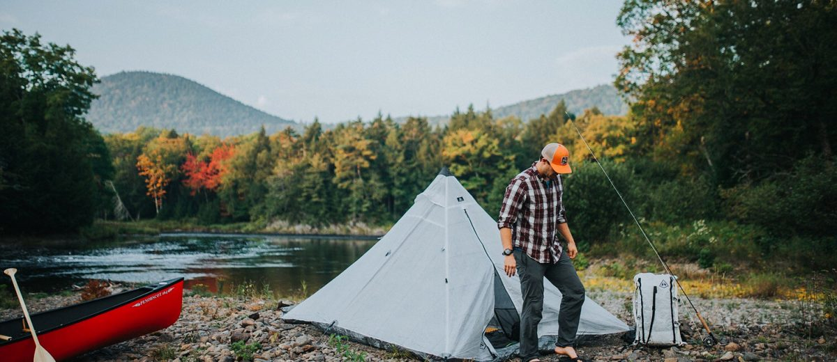 photo of man with tent setup on river with canoe and hiking pack