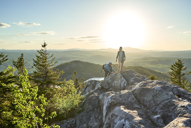 photo of man and woman hiking climbing mountain in maine