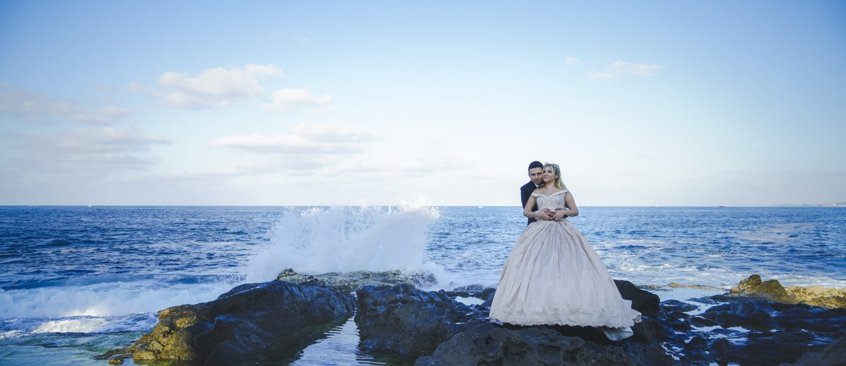 bride and groom poses in front of ocean landscape