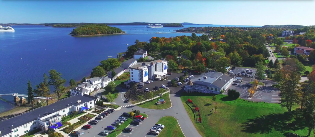 aerial photo of maine atlantic oceanside hotel and cruise ships in the bay