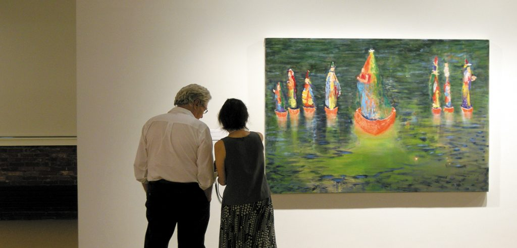 photo of man and woman admiring artwork in exhibit at zillman art museum