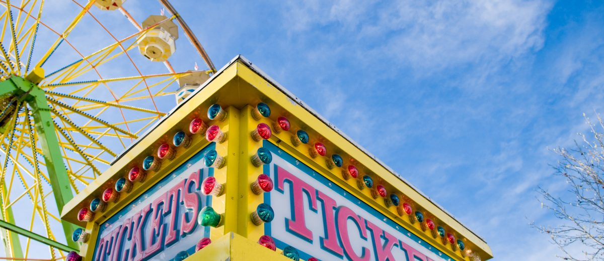Tickets sign at county fair with Ferris wheel and light colored blue sky with white clouds in the background.