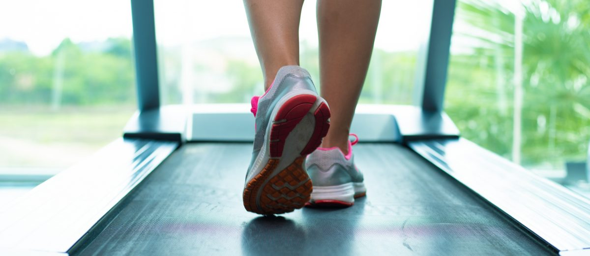 Close up womans legs in pink sneakers on a treadmill in the gym.