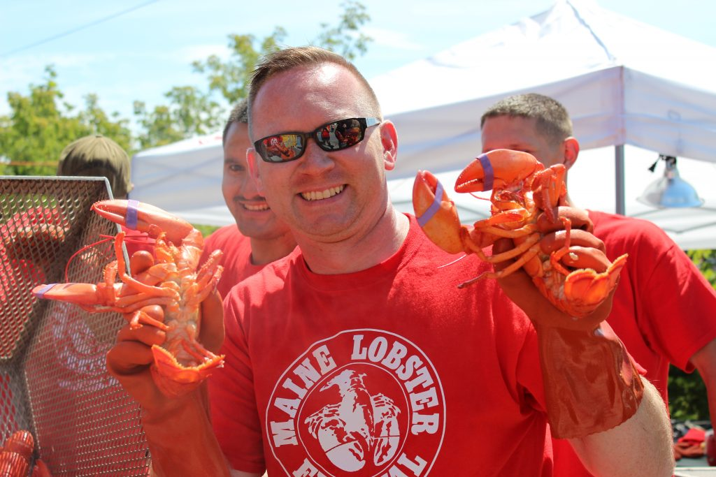 photo of man holding two cooked lobsters from the maine lobster festival
